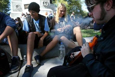 Eddie Curley , right, used a water pipe while smoking with friends during the Boston Freedom Rally on Sept. 17.